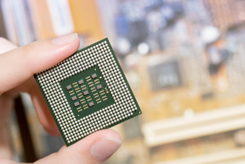Computer processor. In a hand against motherboard stock image