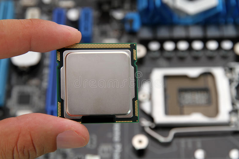 Computer processor. Close-up of a computer processor in hand against motherboard royalty free stock image