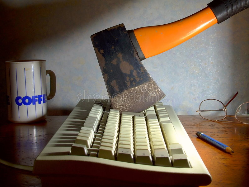 Computer Rage. A computer keyboard with an old hatchet stuck into it stock photography