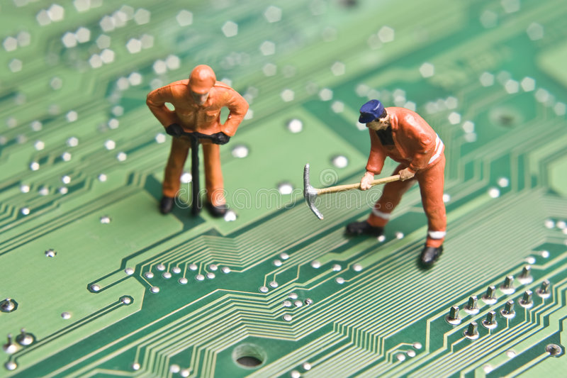 Computer repair. Worker figurines posed to look as though they are working on a computer circuit board