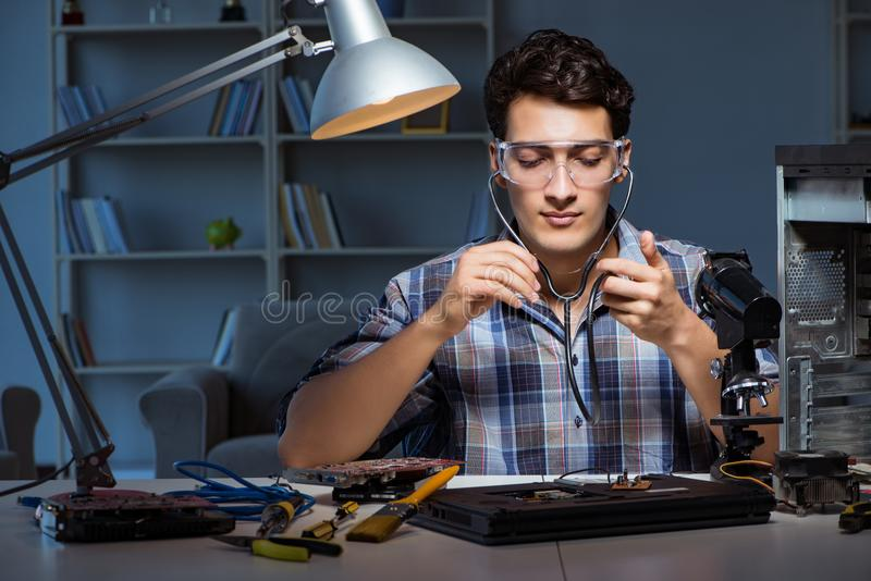 The computer repair concept with man inspecting with stethoscope stock image