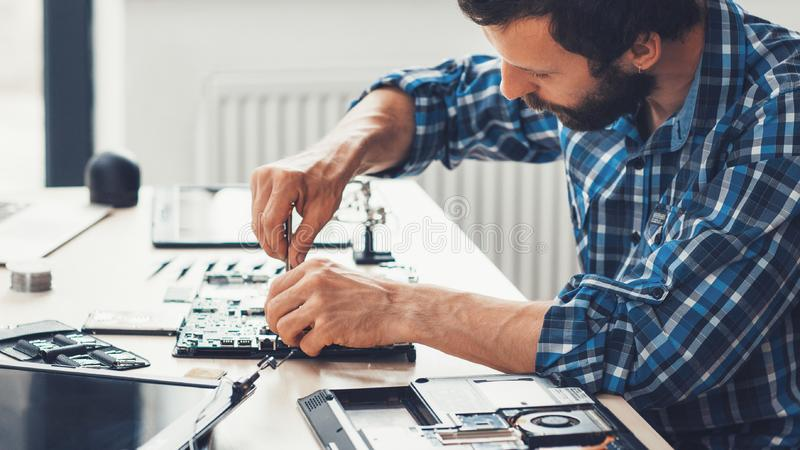Computer repair service electronic hardware support. Computer repair service. Electronic hardware support. Side view of bearded technician fixing damaged laptop stock photo
