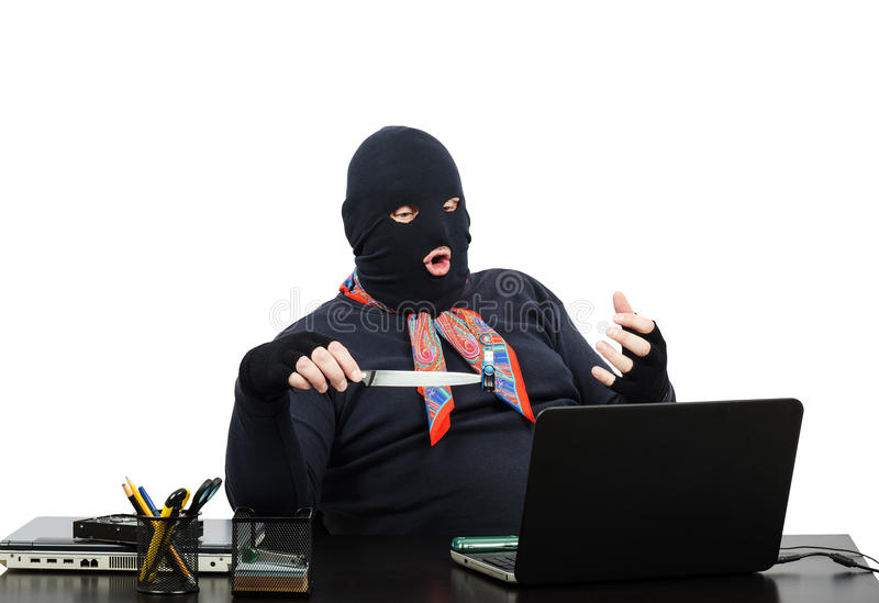 Computer robber holding usb flesh memory on knife. During skype conversation in robbed office stock image