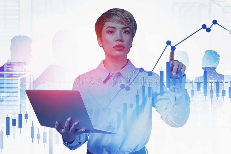 Computer scientist working with digital charts. Smart and beautiful young computer scientist working with digital graph in city with business people silhouettes royalty free stock photography