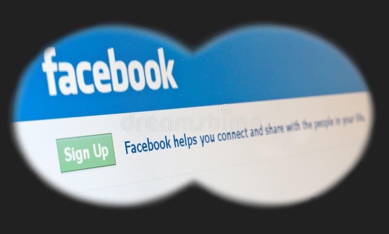 Facebook page seen through binoculars royalty free stock image