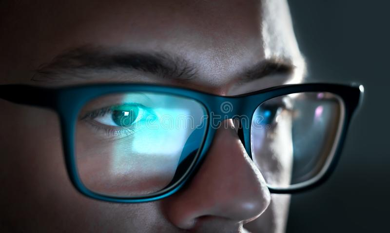 Computer screen light reflect from glasses. Close up of eyes. Business man, coder or programmer working late at night with laptop. Thoughtful focused guy in royalty free stock photos