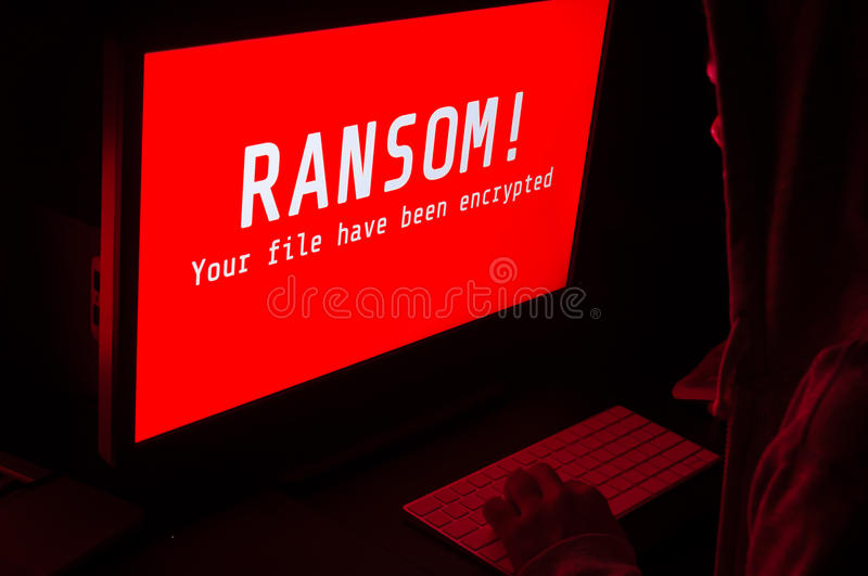 Computer screen with ransomware attacks alert in red and a man k. Computer screen with ransomware attack alert in red and a man keying on keyboard in a dark room royalty free stock photography