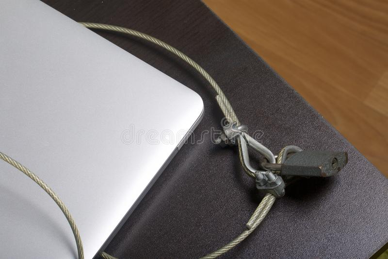 Computer security. Protection of access to data. The laptop is protected by a security cable and a lock. Restricting access to the stock photography