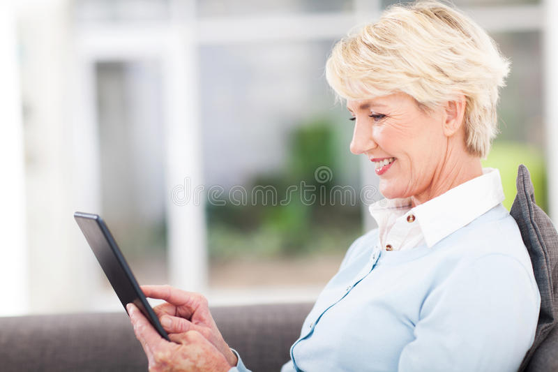 Computer senior della compressa della donna fotografie stock