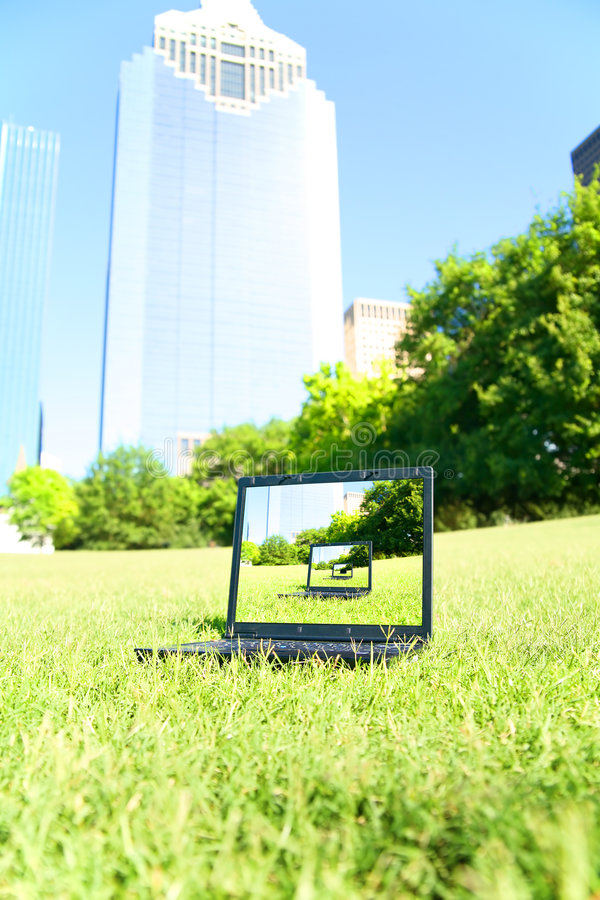 Computer sitzen im im Stadtzentrum gelegenen Park lizenzfreies stockbild