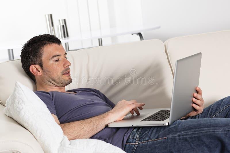 Computer on sofa royalty free stock image