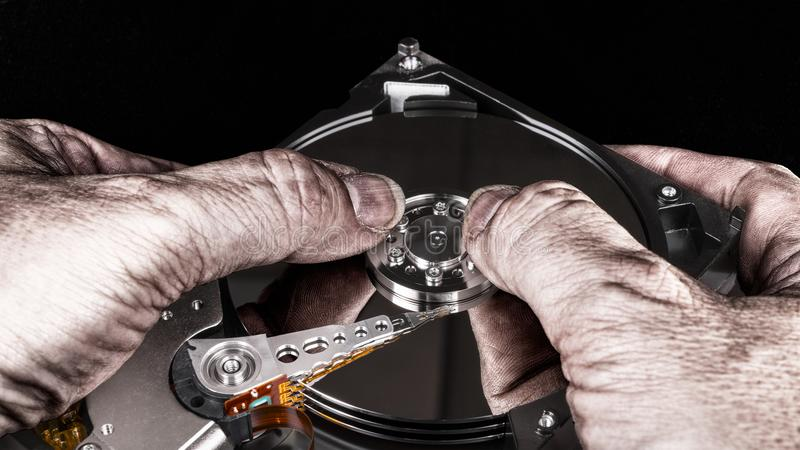 Dirty hands on hard disk drive. Artistic close-up, mirroring, black background. Computer spy with dismantled storage device. Idea of cybercrime, sabotage, theft stock photos