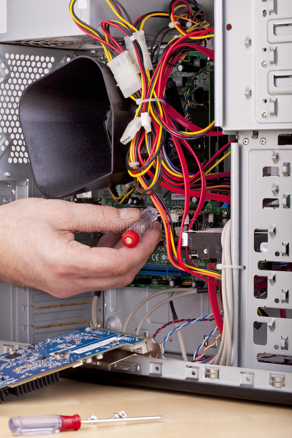 Computer support engineer. Studio-shot of a computer support engineer checking the motherboard of an office computer royalty free stock image