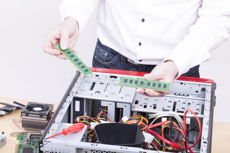 Computer support engineer. Upgrading the RAM ( internal Memory ) chip of an office computer. Studio shot on a white background stock photos