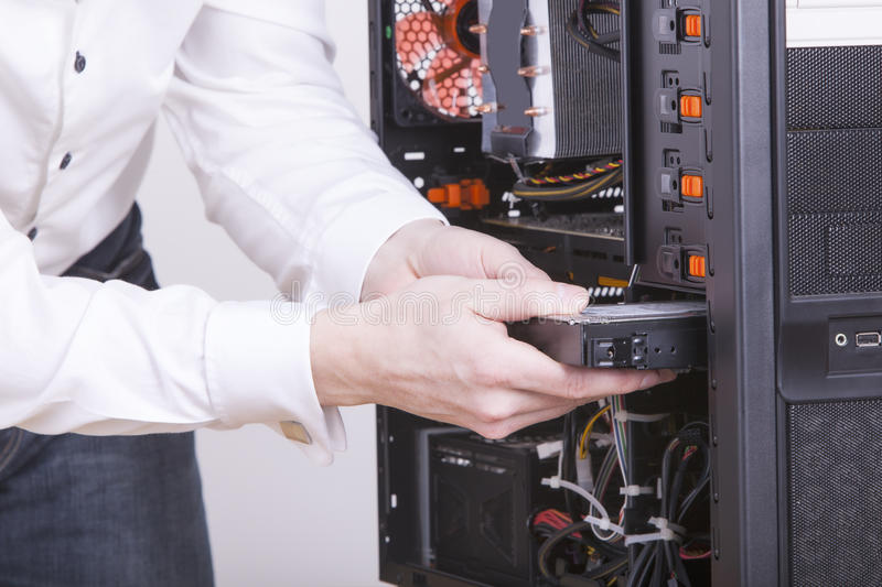 Computer support engineer. Changing the hard drive of an office Computer. Studio shot on a white background royalty free stock images