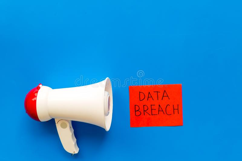 Computer system protection from hacker with data breach copy and speaking trumpet on blue background top view mockup stock photo
