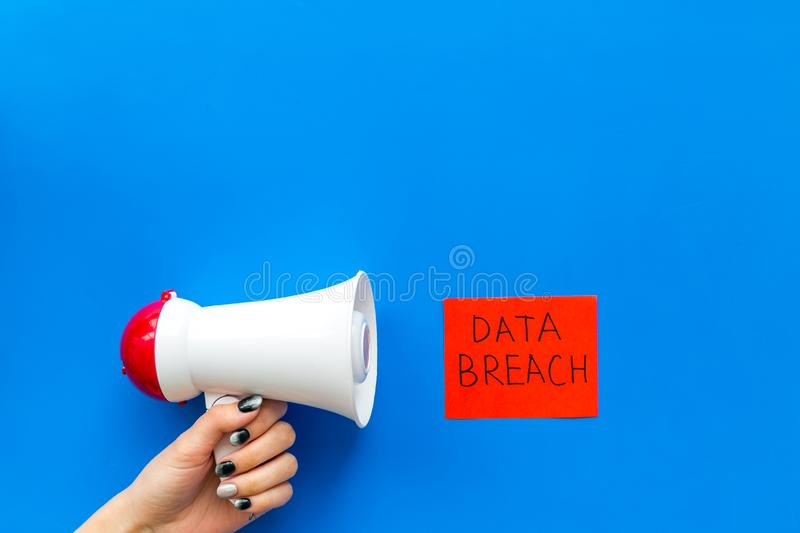 Computer system protection from hacker with data breach copy and speaking trumpet on blue background top view mockup stock photos