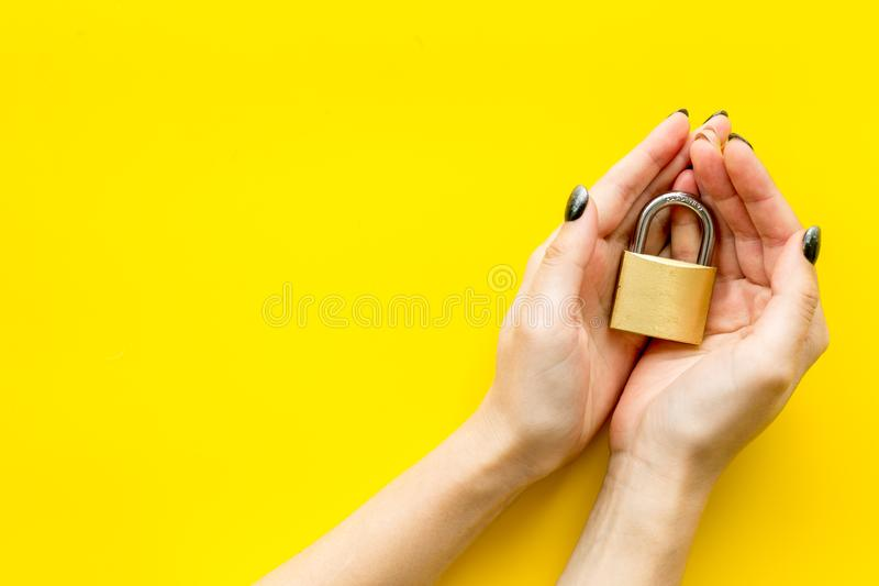 Computer system protection from hacker with locker in hands on yellow background top view space for text royalty free stock photography