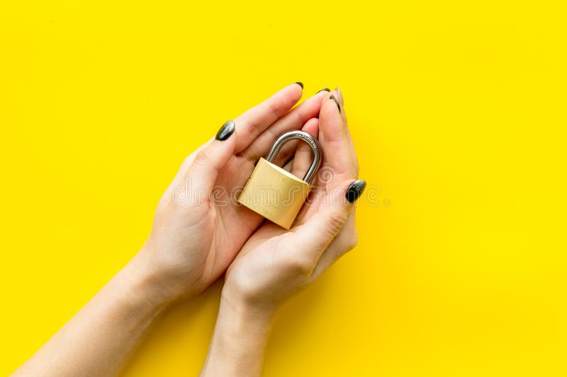 Computer system protection from hacker with locker in hands on yellow background top view space for text royalty free stock image