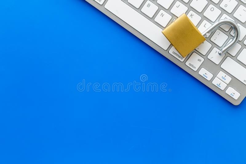 Computer system protection from hacker with locker and keyboard on blue background top view copyspace stock photography