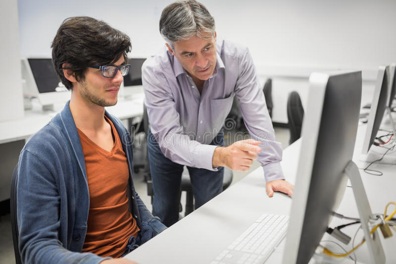Computer teacher assisting a student royalty free stock image