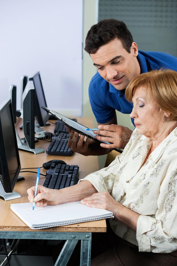 Computer Teacher Holding Clipboard While Senior Woman Writing No royalty free stock images