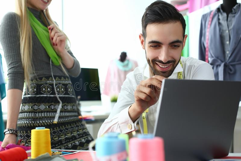 Computer Technology Modern Fashion Sewing Idea. Smiling Man Looking at Laptop Screen. Caucasian Woman Designer Creating Exclusive Garment for Order. People royalty free stock image