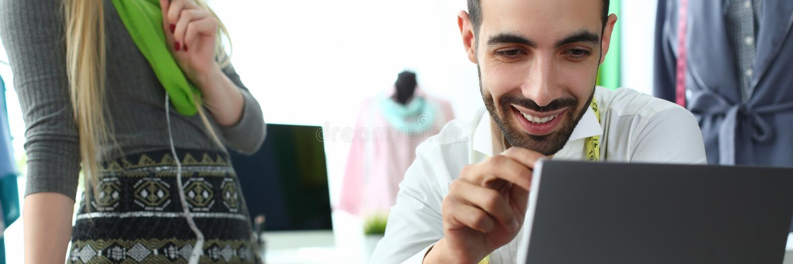 Computer Technology Modern Fashion Sewing Idea. Smiling Man Looking at Laptop Screen. Caucasian Woman Designer Creating Exclusive Garment for Order. People stock photos