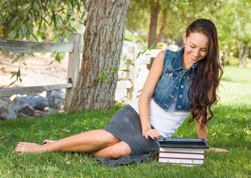 Computer teenager di With Books Using della studentessa della corsa abbastanza mista immagini stock