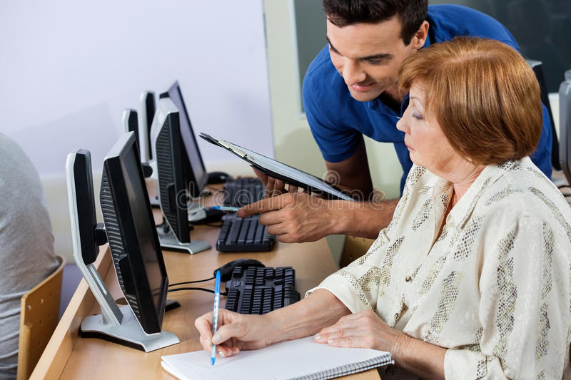 Computer Tutor Holding Clipboard While Senior Woman Writing Note royalty free stock photos