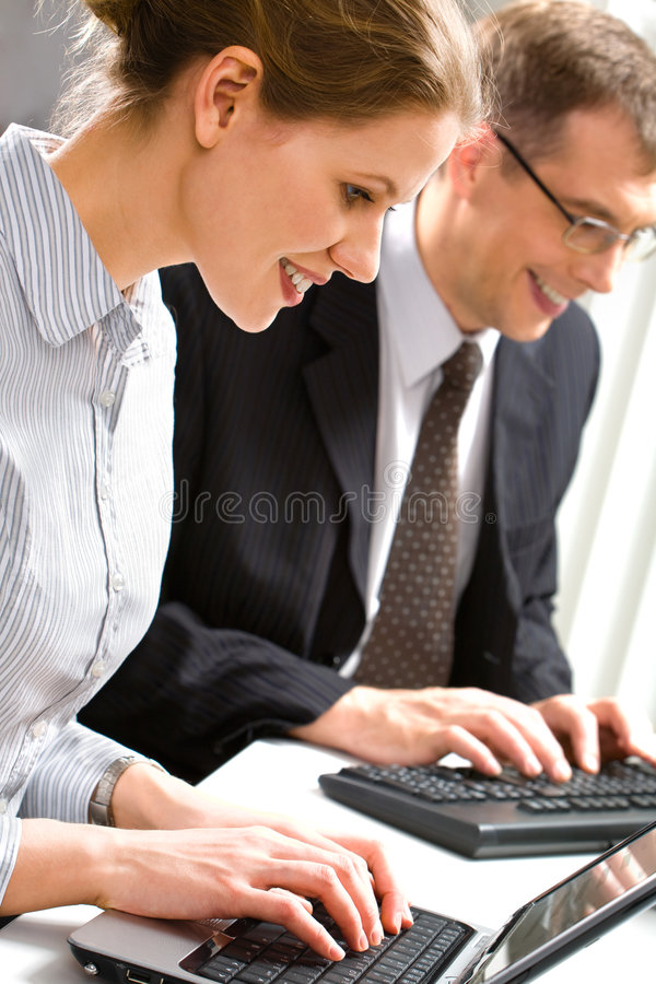 Computer work. Row of business people typing something over laptop and computer