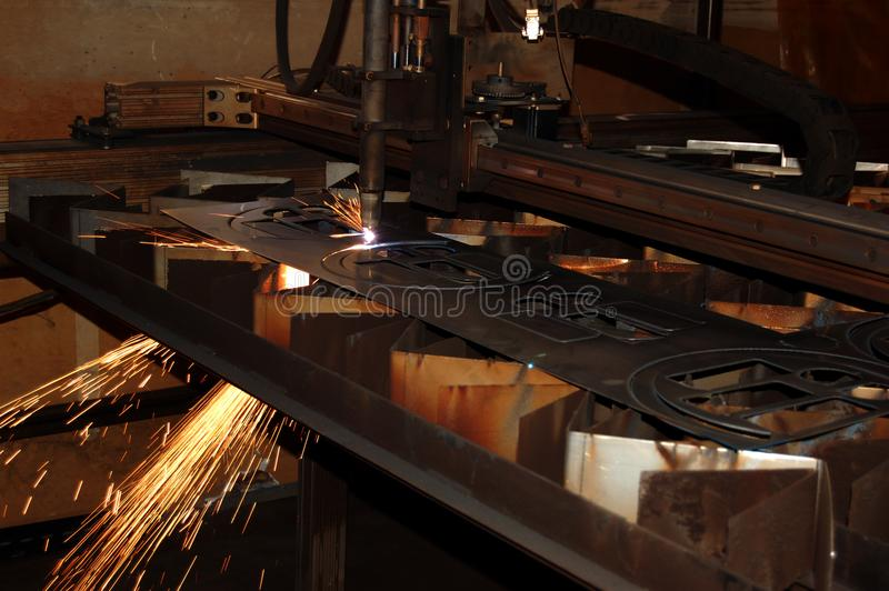 Steel Fabrication. A computerized metal laser cutting machine performs precise intricate cuts out of sheets of stainless steel, producing parts that will be used stock image
