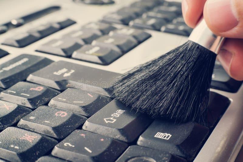Computerkenntnisseinstandsetzer übergibt, überprüft saubere horizontale Ansicht des Laptops des Säuberns der Schlüssel auf der Ta lizenzfreie stockfotos