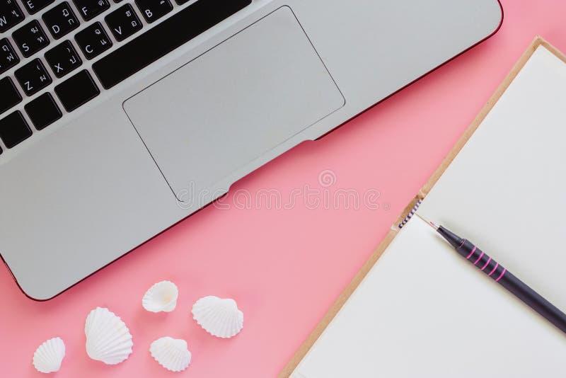 Computerlaptop met een pen, een geopend notitieboekje en overzeese shells  royalty-vrije stock fotografie