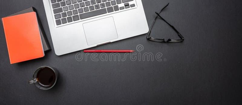 Computerlaptop und -Handy auf schwarzem Farbschreibtisch, Fahne lizenzfreie stockfotografie