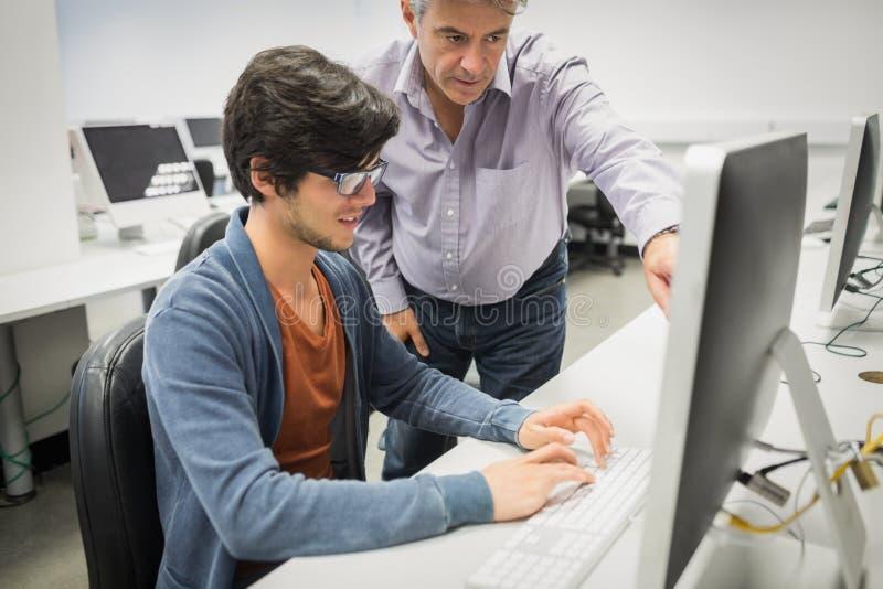 Computerlehrer, der einen Studenten unterstützt stockbild