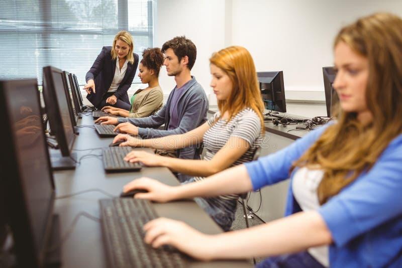 Computerleraar die een mooie student in haar klasse helpen royalty-vrije stock fotografie