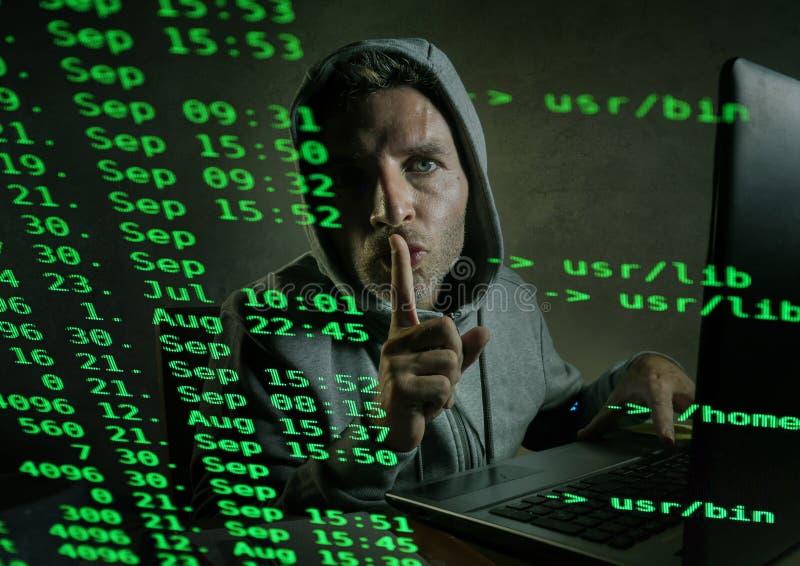 Computerprogrammierermann im Hoodie, der hereinkommenden Code des Systems schreibend auf dem zerhackenden Laptop zerhackt und ill lizenzfreies stockfoto
