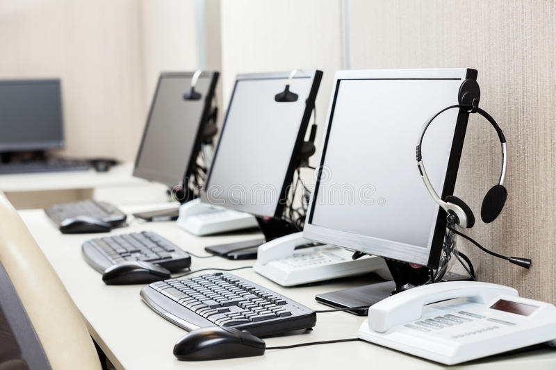 Computers With Headphones On Desk. Row of computers with headphones on desk at call center royalty free stock photos