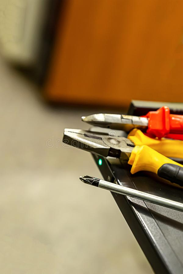 Computerserver-Reparaturwerkzeug liegen ein Stapel am Rand der Metalltabelle Seth-Zangenschraubenzieher lizenzfreie stockfotografie