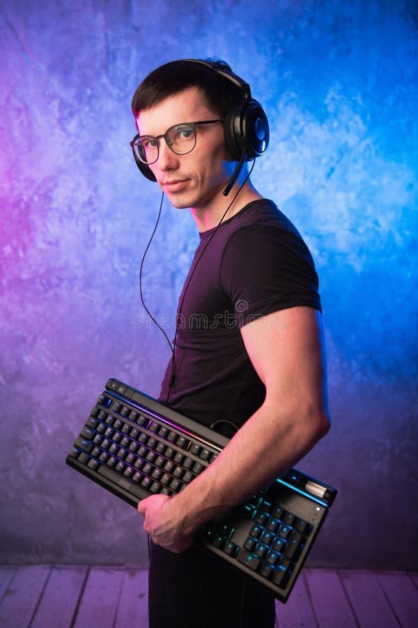 Computersonderling mit Tastatur über buntem Rosa und blauer beleuchteter Neonwand lizenzfreie stockbilder