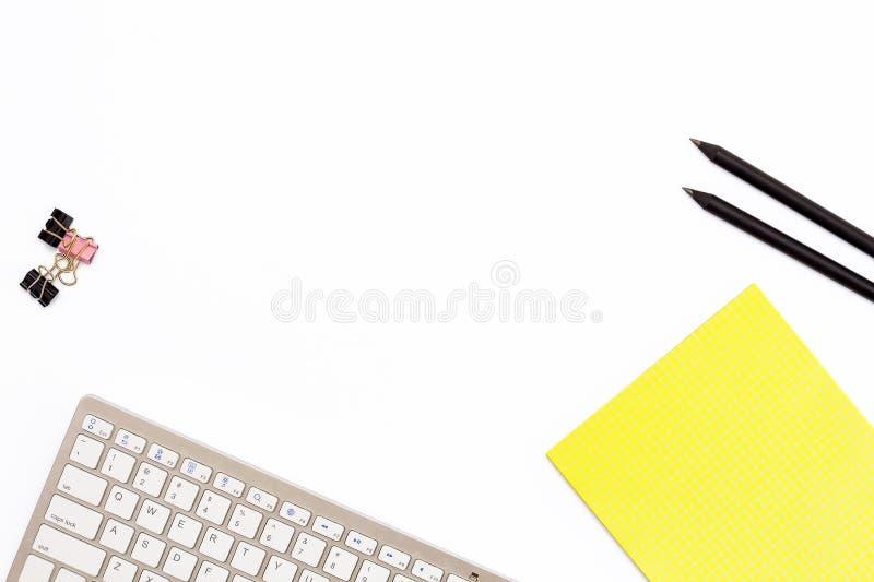 Computertastatur, eine gelbe Auflage, zwei schwarzer Bleistift und Klipp für Papier auf weißem Hintergrund Minimales Geschäftskon stockbild