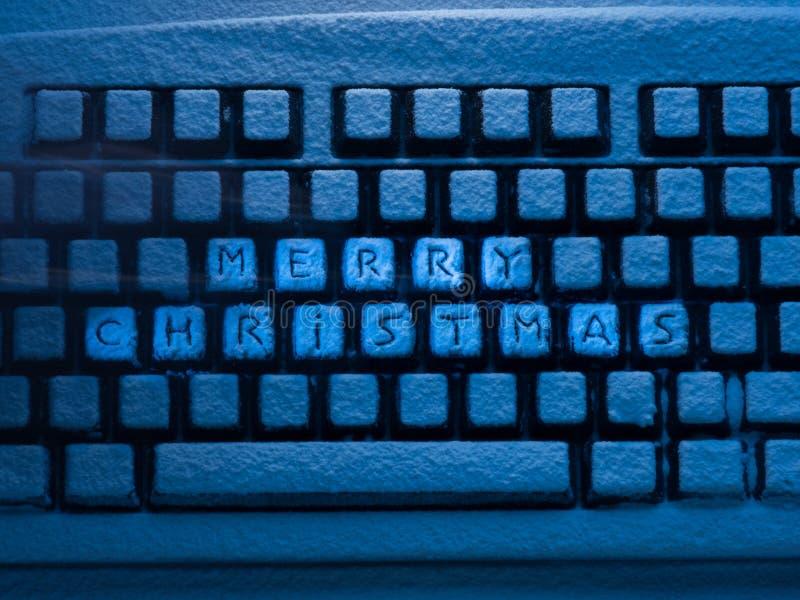 Computertoetsenbord met het van letters voorzien vrolijke die Kerstmis op knopen met sneeuw worden behandeld door blauw neonlicht stock afbeelding