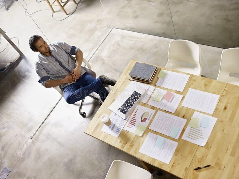 Comtemplando al hombre de negocios asiático que se sienta solamente en sala de reunión imagenes de archivo