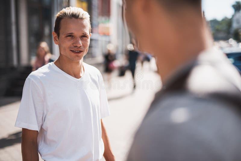 Comunicação masculina positiva com o camarada na cidade fotografia de stock royalty free