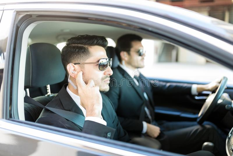 Comunicación de Using Earpiece For del oficial en coche foto de archivo libre de regalías