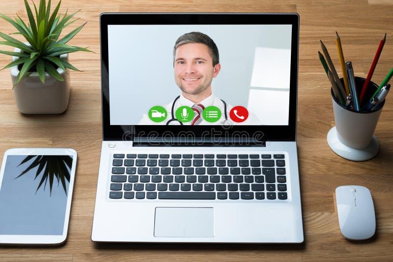 Comunicación del doctor Smiling While Video en el ordenador portátil en hospital fotografía de archivo libre de regalías
