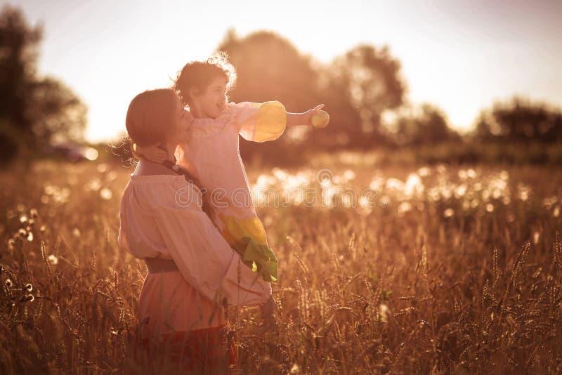 Comunicación feliz de la madre con la hija en un campo de trigo imagenes de archivo