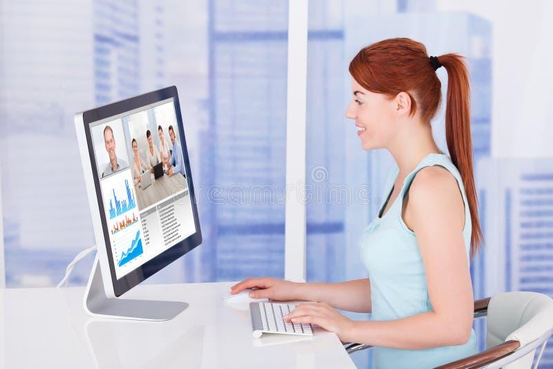 Comunicación video de la empresaria con el equipo en el ordenador foto de archivo libre de regalías