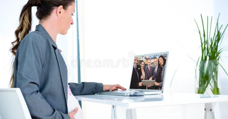 Comunicación video de la empresaria embarazada con los socios en el ordenador portátil en la oficina foto de archivo libre de regalías